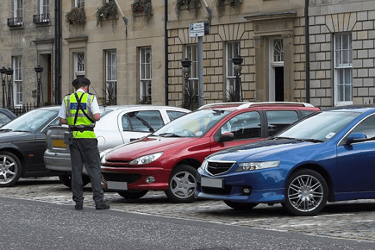Traffic warden giving parking tickets