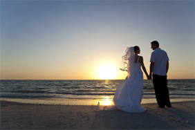 A bride and groom on the beach at sunset
